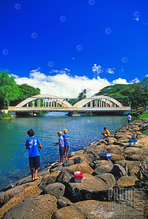 Children fish in the Anahulu River in the historic town of Haleiwa on oahu's north shore. Landmark double-arched bridge in the background.