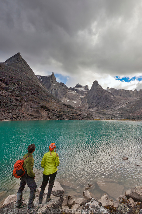Hikers view the dramatic granite spires of the Arrigetch Peaks reflecting in a mirror calm mountain lake, Gates of the Arctic National Park, Alaska.
