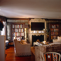Twin bookcases framed by antique mirrored tiles flank a central flatscreen TV incorporated into the mantelpiece