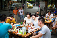 "A group of friends who live in the neighborhood eat at He Wang Shi Chuan Chuan Xiang Huo Guo, a skewer-style hotpot restaurant popular with locals on Tiyu Road in Chongqing, China. The girl in white, who asked not to be named, said that it's one of their favorite places the hotpot flavor is so good.  ""We like the atmosphere. It's a typical Chongqing place: friends sit together and it's hot out and you all sweat together."" She works in real estate and thinks that places like this won't survive as neighborhoods develop.<br /> <br /> Individual servings of meat, vegetables, and tofu, are placed on skewers which diners choose to add to their table's hotpot. The restaurant, which has many favorable online reviews, often has a long wait for tables."
