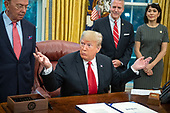 "United States President Donald J. Trump takes a reporter's question after signing S. 3508, the ""Save Our Seas Act of 2018"" in the Oval Office of the White House in Washington, DC on Thursday, October 11, 2018.  Looking on from behind the President are: US Secretary of Commerce Wilbur L. Ross, Jr., left, US Senator Dan Sullivan (Republican of Alaska), center right, and Julie Fate, wife of Senator Sullivan, right.<br /> Credit: Ron Sachs / CNP"