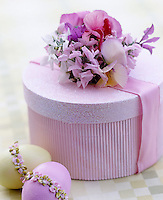 A gift wrapped box decorated with flowers and ribbons with two Easter eggs