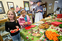 STAFF PHOTO JASON IVESTER --12/12/2014--<br /> MJ Peterson (left), 7, and Abby Jaramillo, 7, both of Lowell, fill their plates with refreshments on Friday, Dec. 12, 2014, inside the Lowell Historical Museum. The museum hosted a Christmas open house to visitors.