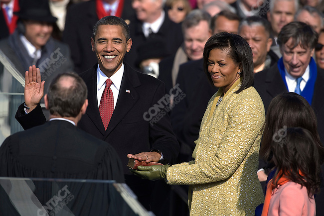 President Barack Obama, accompanied by his wife, Michelle, and his daughters, Malia and Sasha, is sworn into office by Chief Justice John Roberts at The Capitol Building. Washington, DC, January 20, 2009.
