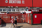 Two home supporters walking past the main entrance to the stadium on Braemar Road pictured before Brentford hosted Leeds United in an EFL Championship match at Griffin Park. Formed in 1889, Brentford have played their home games at Griffin Park since 1904, but are moving to a new purpose-built stadium nearby. The home team won this match by 2-0 watched by a crowd of 11,580.