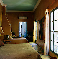 In the double bedroom the walls are painted yellow ochre and a pair of blue doors lead to the en suite bathroom. On the walls are splendid Uzbek and Moroccan textiles