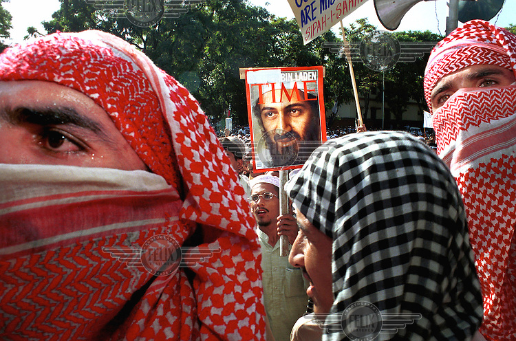 © Piers Benatar / Panos Pictures..Islamabad, Pakistan. 28 September 2001...Demonstrators at a pro-Taliban rally mask their faces and hold up the cover of Time Magazine with a portrait of Osama Bin Laden. The rally was organised by the 'Sipah-i-Sahaba' fundamentalist Islamic group. A few days earlier such meetings had been officially banned by the government of Pakistan. Tensions were high in the wake of the September 11th terrorist attacks on the United States. Pakistan's President Musharraf angered many of his countrymen by joining America's alliance against terrorism.