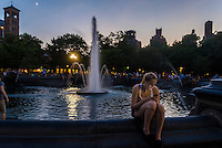 New York, NY - 20 July 2015 - A woman sits by the fountain and examines her cell phone on a summer evening in Washington Square Park Stacy Walsh Rosenstock/ALamy