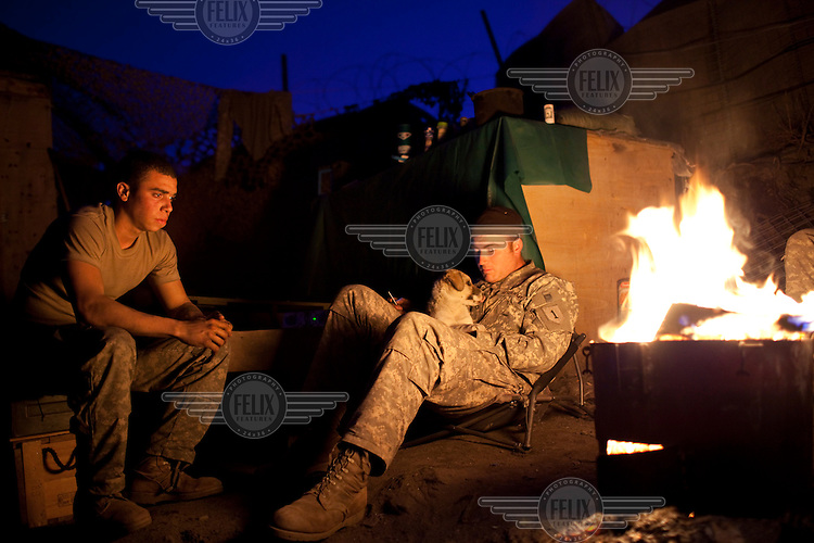 US Army Soldiers from Viper Company 126, 1st Platoon, relax by a fire at Restrepo Firebase in the restive Korengal Valley close to the Pakistan border in Kunar. Restrepo, a remote outpost, is known as one of the most violent places in Afghanistan. Located in the Korengal Valley it comes under fire on a daily basis from Anti-Afghan Forces in the local villages and mountains.
