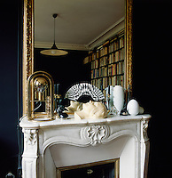 Graphic patterns, added to a simple palette of black and white create an elegant combination. A gilt-framed mirror hangs above a marble fireplace in the study with its built-in bookshelves