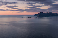 Summer twilight over sea and distant mountains of Vestvågøy from summit of Hornet, Flakstadøy, Lofoten Islands, Norway