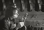 Scan of vintage black & white print. J.R. Judd tuning a violin. Negative file#85-239-0 #16. 1985