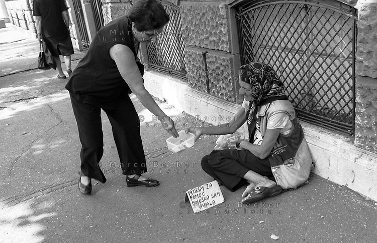 Belgrado, una donna fa elemosina a una mendicante mentre un'altra signora, dopo lo stesso gesto, si allontana --- Belgrade, a woman giving alms to a beggar while another lady, after the same act, walks away