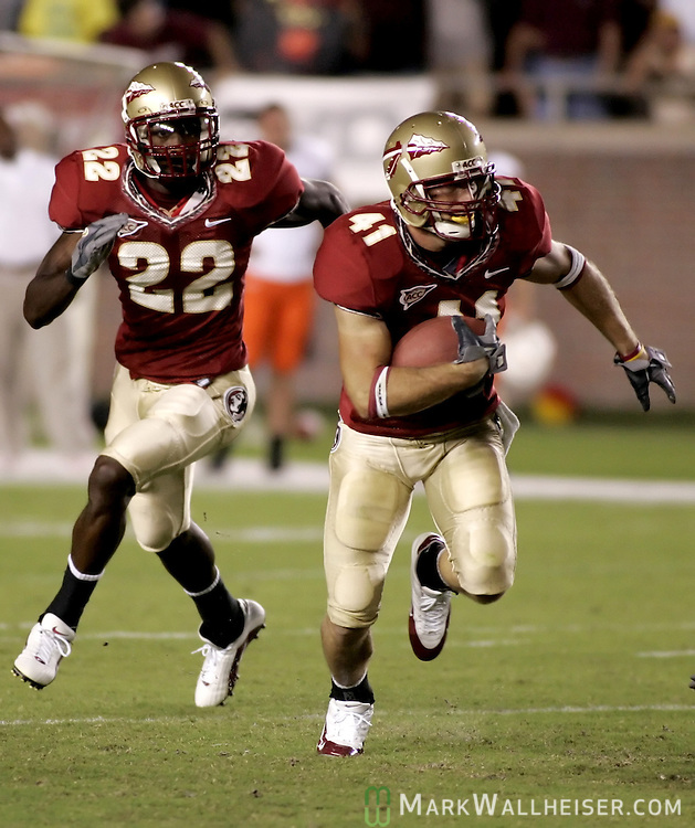 Florida State University defender Kyler Hall intercepts a first quarter pass by University of Miami quarterback Kyle Wright during their NCAA season opener in Tallahassee, Florida September 5, 2005. At left is FSU free safety Pat Watkins. Hall returned the ball 37 yards.