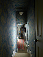 The passageway and the bedroom are decorated in blue and gold wallpaper.