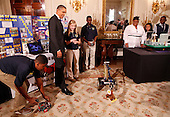 United States President Barack Obama watches a robot with students  Robert Knight, III (L),Morgan Ard, and Titus Walker, 8th grade students at Monroeville Jr. High School in Monroeville, Alabama who won high honors at the South BEST robotics competition, while touring student science fair projects on exhibt at the White House in Washington, D.C. on February 7, 2012.  Obama hosted the second White House Science Fair celebrating the student winners of science, technology, engineering and math (STEM) competitions from across the country. .Credit: Molly Riley / Pool via CNP