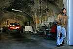 William, a car mechanic, at the entrance to his workshop in Ramallah, West Bank.