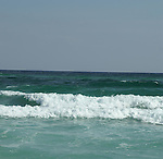 The shallow clear water of the Gulf of Mexico and the white sugar sand of Pensacola Beach produce clear green waves unique to the area.