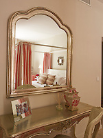 A guest bedroom is furnished with a pretty gilt dressing table and matching mirror