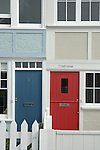 Close-up of  two terraced cottages with red and blue doors, Whitstable, Kent