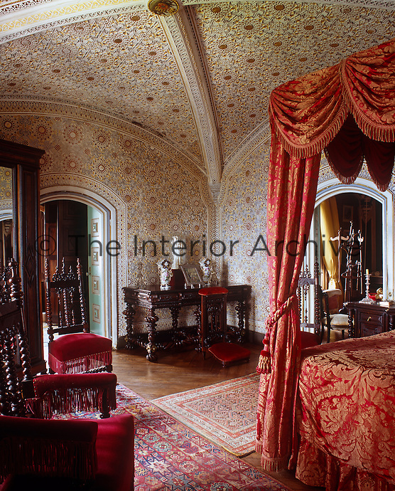 Ornate painted stucco work in Moorish geometric patterns covers the walls and ceiling of this vaulted bedroom
