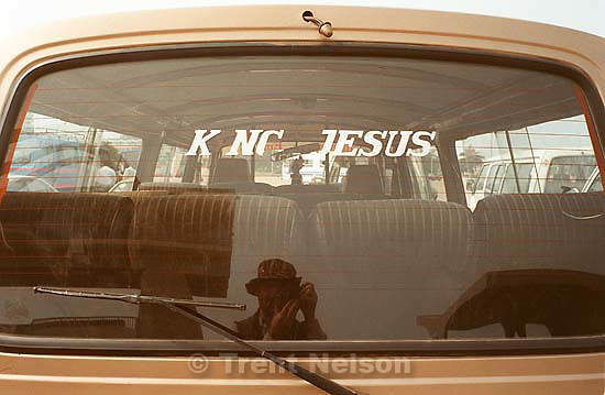 Van with &quot;King Jesus&quot; sticker and Trent Nelson reflection in Independence Square during LDS prophet Gordon B. Hinckley's visit.<br />