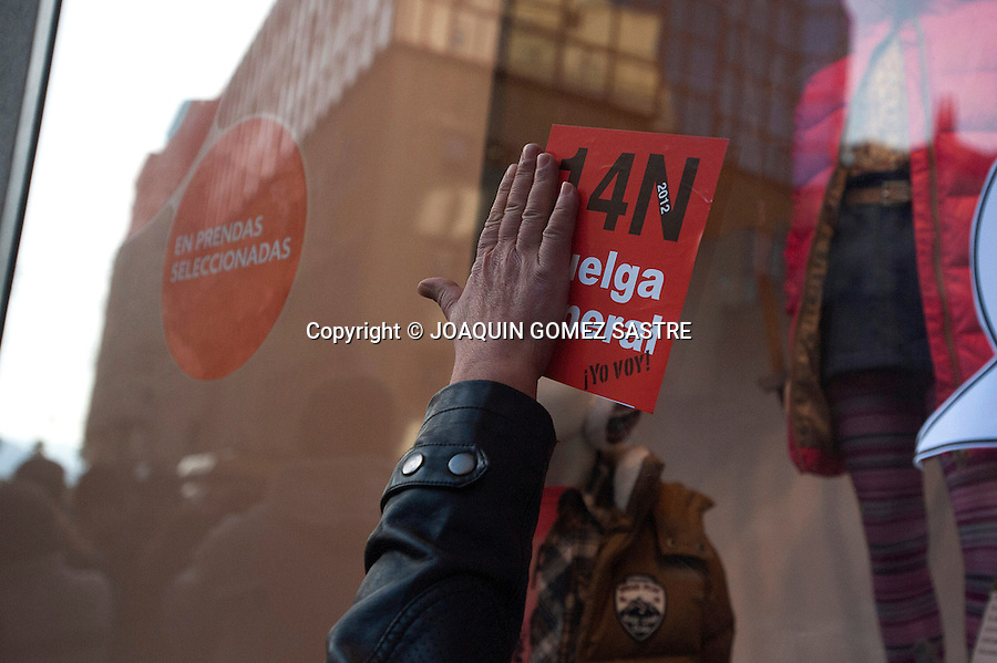 A member of a squad puts a sticker on the general strike of 14-M in a showcase of Santander (SPAIN). Strikes and workers' protests have multiplied because of government cuts.photo © JOAQUIN GOMEZ SASTRE