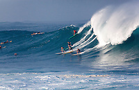 Surfers riding a large wave at Waimea Bay, North Shore, Oahu
