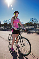 Attractive female biker on Lamar Street Pedestrian Bridge ponders her mountain biking excursion on the Lady Bird Lake Hike and Bike Trail in downtown Austin, Texas.