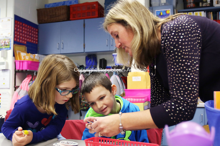BEACON FALLS CT. 20 November 2015-112015SV01-From left, Rebecca Armstrong, 7, and Jake Trumbley, 7, check out their paper donuts with their 2nd grade teacher Colleen Gabriel during a donut production exercise for a Junior Achievement lesson at Laurel Ledge Elementary School in Beacon Friday. It was Junior Achievement day at the school. <br /> Steven Valenti Republican-American