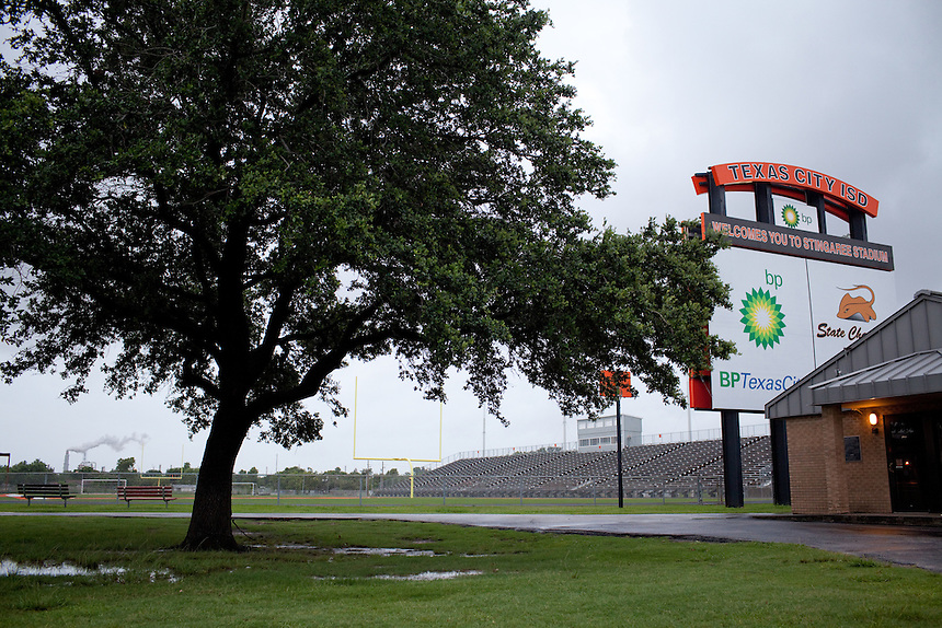 A large BP advertisement sits on the scoreboard at the Texas City High School football stadium.  The massive BP refinery is nearby.