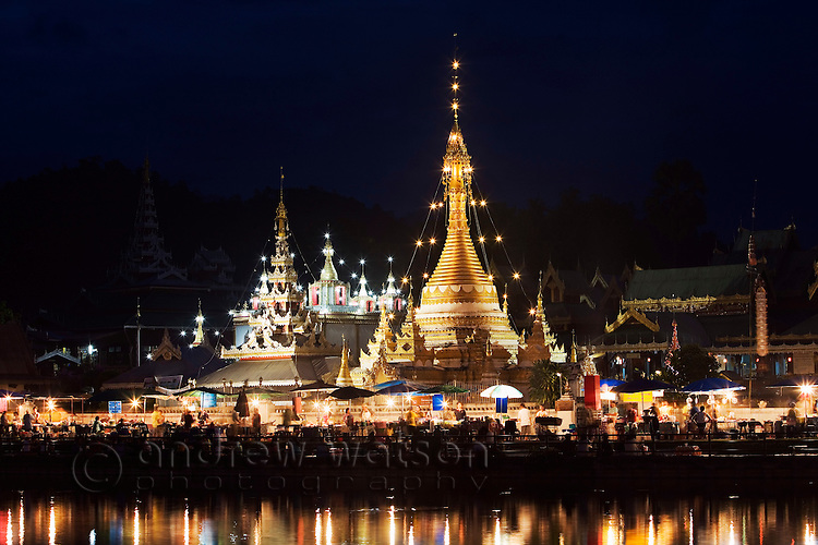 Night market and the chedis of Wat Jong Kham and Wat Jong Klang reflected in the waters of Nong Jong Lake.  Mae Hong Son, Mae Hong Son province, THAILAND.