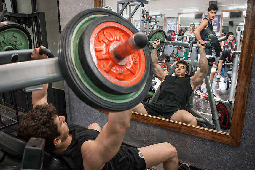 Masih Farzaneh, an Iranian bodybuilder, lifts the weight at a gym at Jolfa, the Armenian quarter of Isfahan. In a men-centered society as Iran, for many Iranian men, masculinity is a pride to be pursued.