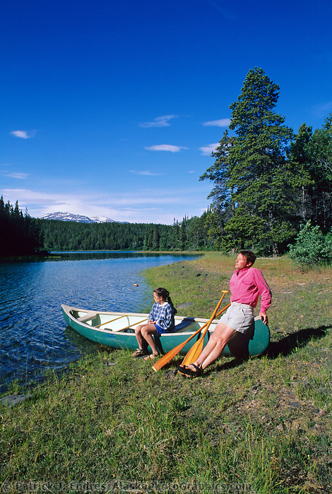 Man and young girl rest in the morning sun while canoeing on Atlin Lake, Atlin, BC Canada