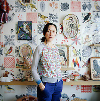 A portrait of artist, Nathalie Lété standing in front of a wall of hand-painted tiles