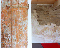 The texture and pattern of a wooden cupboard door with layers of peeling paint juxtaposed against a half-plastered brick wall