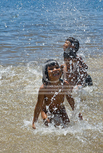 Xingu Indigenous Park, Mato Grosso State, Brazil. Aldeia Yawalapiti; children enjoying  a bathe in the river, splashing the water and smiling.
