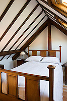 A cosy guest bedroom has been tucked under the stunning beamed ceiling of the attic and is brightly lit by two skylights let into the roof