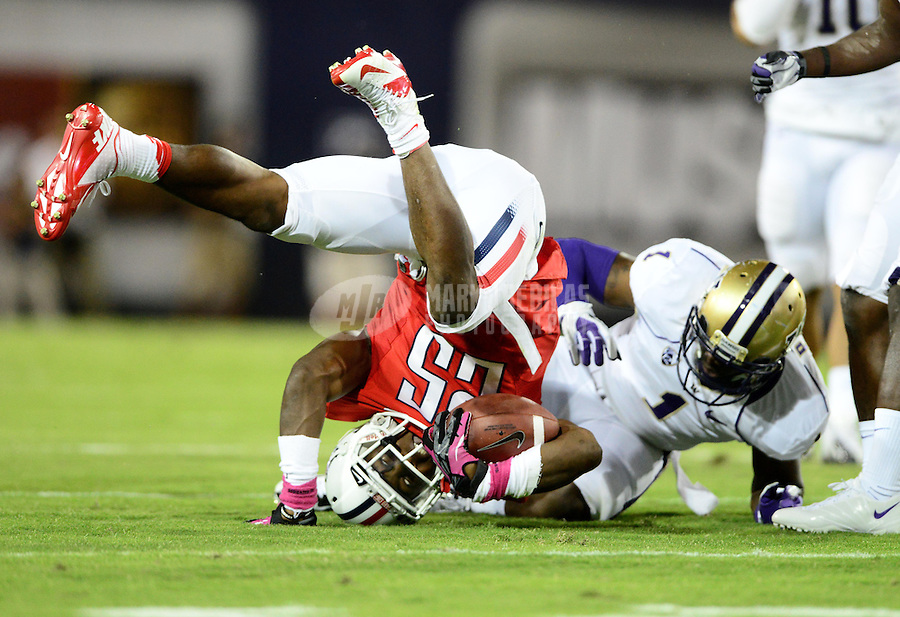 Oct. 20, 2012; Tempe, AZ, USA; Arizona Wildcats running back (25) Ka'Deem Carey is flipped as he runs the ball in the first quarter against the Washington Huskies at Arizona Stadium. Mandatory Credit: Mark J. Rebilas-