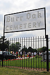 People gather by the entrance to the Burr Oak Cemetery, one of the oldest and most historic black American cemeteries on the outskirts of Cook County, the same day four cemetery managers and caretakers were arrested on felony charges of disinterring and dismembering bodies at the cemetery in order to resell the plots to unsuspecting members of the public in Alsip, Illinois on July 9, 2009.