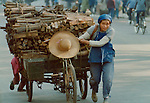 Woman pulling a cart full of fire wood.Pictures taken in Canton China in 1977 at the time of the cultural revolution.