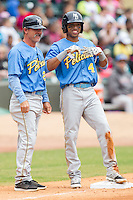 Myrtle Beach Pelicans manager Joe Mikulik (25) smiles along with Chris Garia (4) after Garia hit a triple against the Winston-Salem Dash at BB&T Ballpark on May 7, 2014 in Winston-Salem, North Carolina.  The Pelicans defeated the Dash 5-4 in 11 innings.  (Brian Westerholt/Four Seam Images)