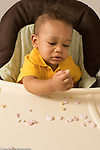 10 month old baby boy sitting in high chair pincer grasp picking up pieces of snack food
