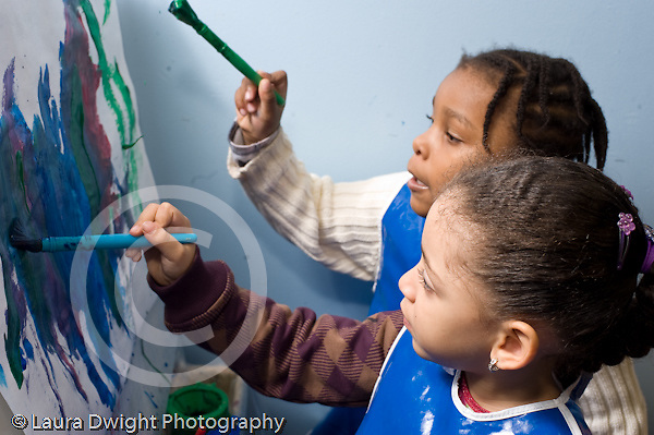 Educaton preschool 4-5 year olds art activity painting at easel two girls at work on the same painting one girl talking horizontal