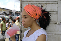 Young lady enjoys her refreshment during the busy hours of the last day of 2010 in the city of  Paramaribo.....End of year 2010 celebrations on the streets of Paramaribo. Suriname is one of biggest consumer in South America that using firecrackers, fireworks ( also locally known as pagara ) for celebrations, especially for end of every years and also beginning of every new Chinese Years.