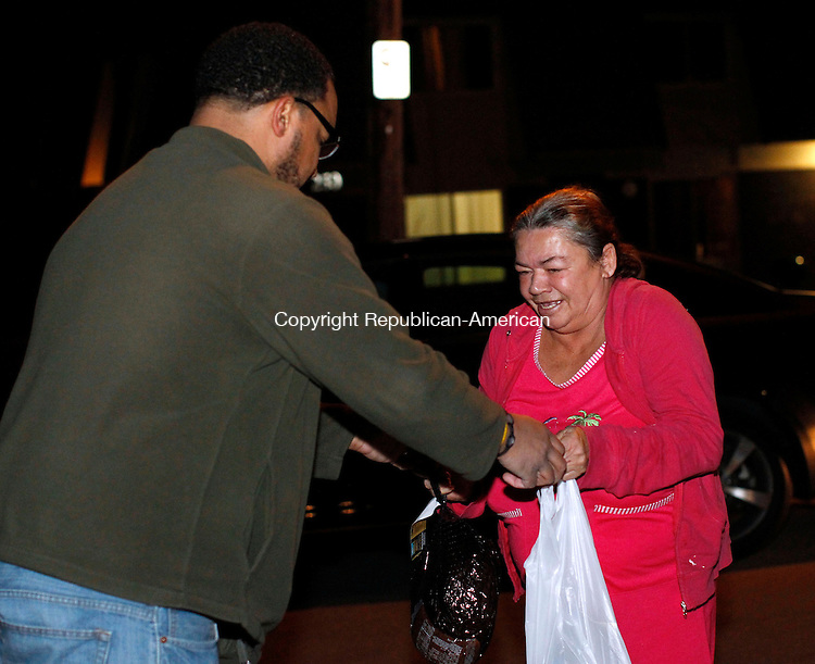 """Waterbury, CT-11 December 2012-121112CM04-  Justus Johnson, with Positive Energy hands a bag of food to Awilda Caraballo outside the Northwoods Apartments Tuesday night in Waterbury.  Joe Ventura, President of Positive Energy, who grew up in the apartments, purchased the food items along with Guy Ferrialo the companies CFO.  This is the second year Ventura and his staff have distributed the items to the community.  Ventura said he's been fortunate to be able to give back to his old neighborhood.  """"It's about not forgetting where you came from."""" he said.  Ventura added he hopes the good gesture might inspire others.  The group handed out 50 bags which included a ham, canned vegetables soup and dessert.  The donated items were gone in less then 30 minutes.  Christopher Massa Republican-American"""