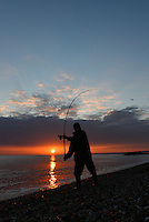 Lone sea angler casting from the beach at Hurst Spit, Hampshire at sunset