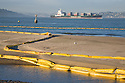 Oil spill containment booms (yellow) line the sands and waters of Crissy Field as a loaded Horizon Lines container ship enters San Francisco Bay (11/12/07). On November 7, 2007 the Cosco Busan container ship spilled an estimated 58,000 gallons of bunker fuel into San Francisco Bay after striking a tower of the San Francisco-Oakland Bay Bridge.