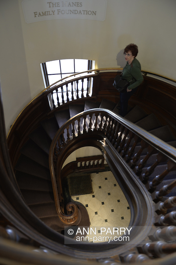 Roslyn, New York, USA. January 2, 2015. Visitor Pat Dillon descends the elongated spiral wood staircase at the Nassau County Museum of Art in Long Island.