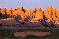 69SDBD_01 - USA, South Dakota, Badlands National Park, North Unit, Sunrise light on wall of eroded, layered sediments above spring green prairie grass, near Castle Trail.